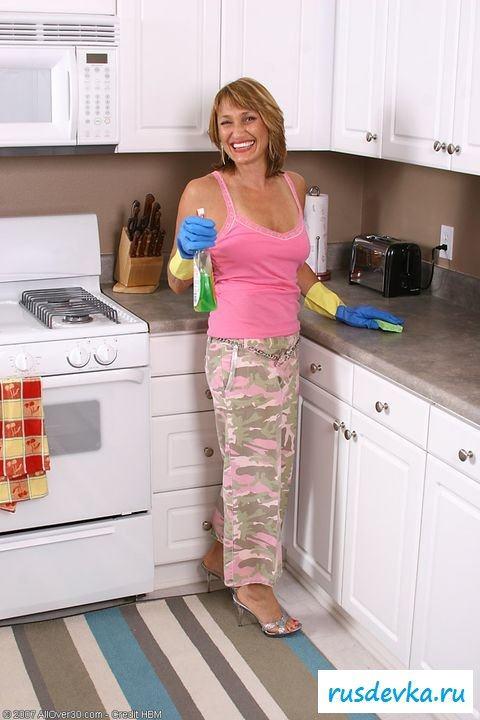 Голая женщина убирается на кухне